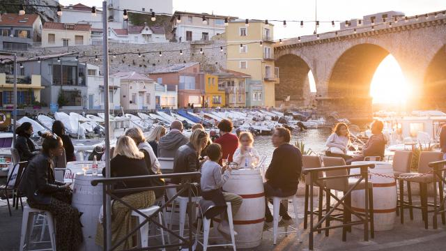 Aperitif au Vallon des Auffes à Marseille, personnes assisent, coucher de soleil en arrière plan