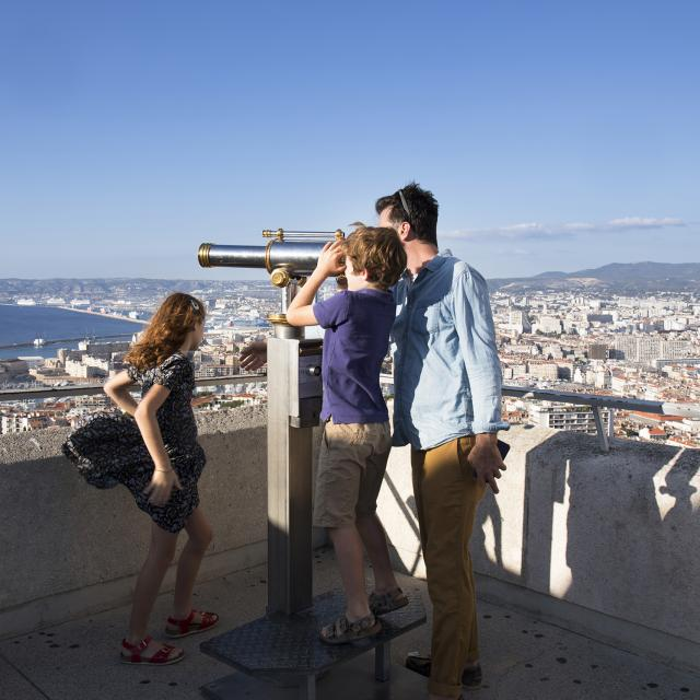 Visite en famille de notre Dame de la garde, enfant qui regarde dans la longue vue, Marseille en arrière plan
