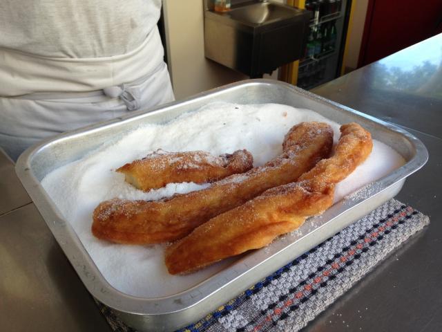 un plat en métal avec 3 gros chichis frégis dans du sucre en poudre d'un kiosque situé dans le quartier de l'Estaque à Marseille