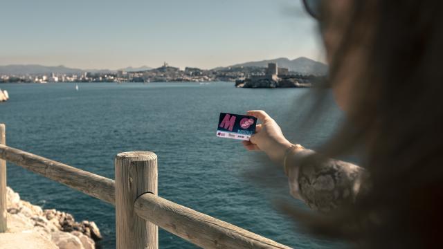 Femme tenant un citypass Marseille face à la mer