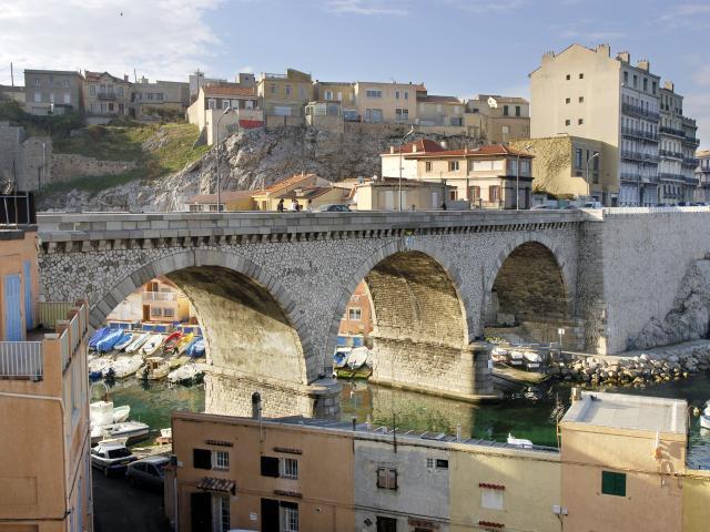 Vue sur le Pont et ses arcades de le Corniche et derrière on apercoit quelques barques du port du Vallon des Auffes à Marseille et en dernier plan la ville et ses habitations