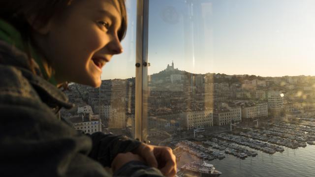 Enfant dans la Grande Roue du Vieux-Port, qui regarde par la vitre. Notre Dame de la Garde en fond.