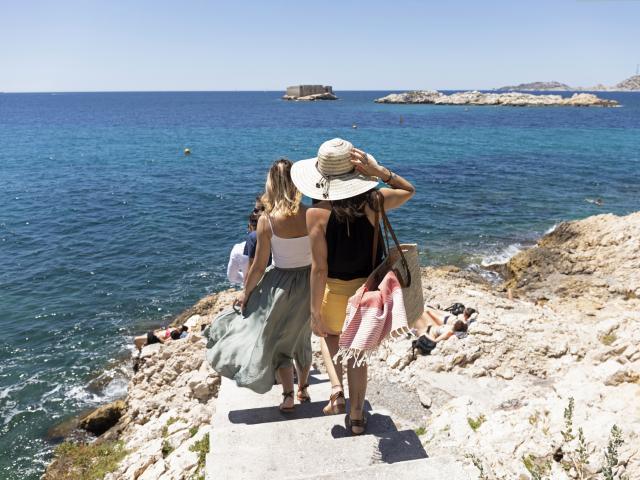 Malmousque à Marseille, groupe d'amies qui marchent sur les rochers à face à la mer