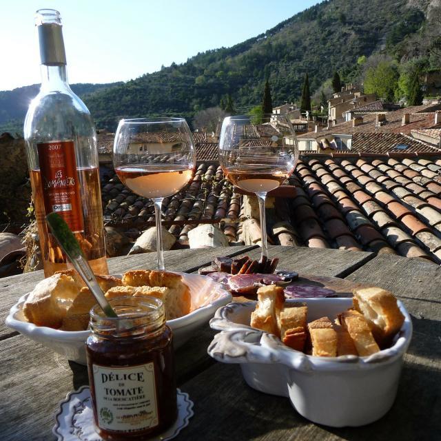 table apéritif, verre de rosé, pain et charcuterie, vue sur les toits et les colline
