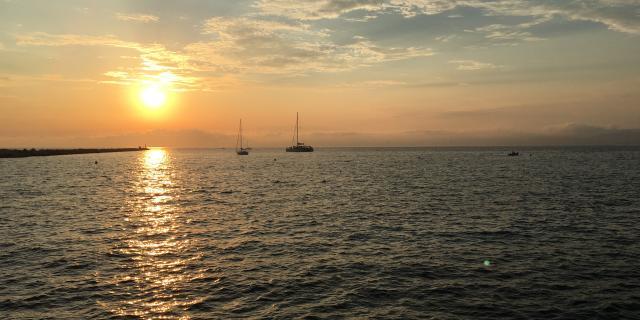 Vue sur la mer et les bateaux face au coucher de solei