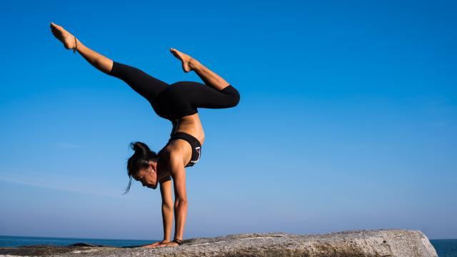 femme qui fait du yoga face à la mer