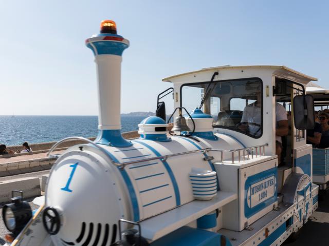 Petit train touristique sur la Corniche Kennedy, vue mer en arriere plan