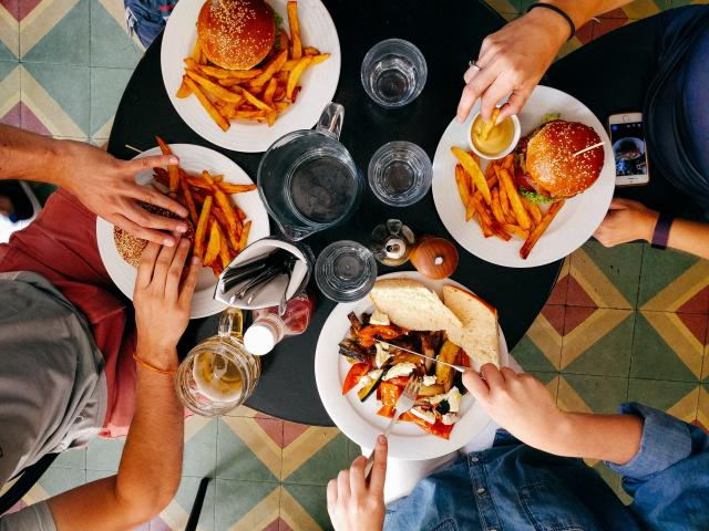 Quatre personnes qui mangent des frites et hamburgers à table