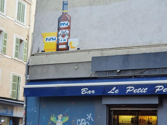 Rue du cours Julien avec oeuvre street art space invader d'un verre et d'une bouteille de pastis