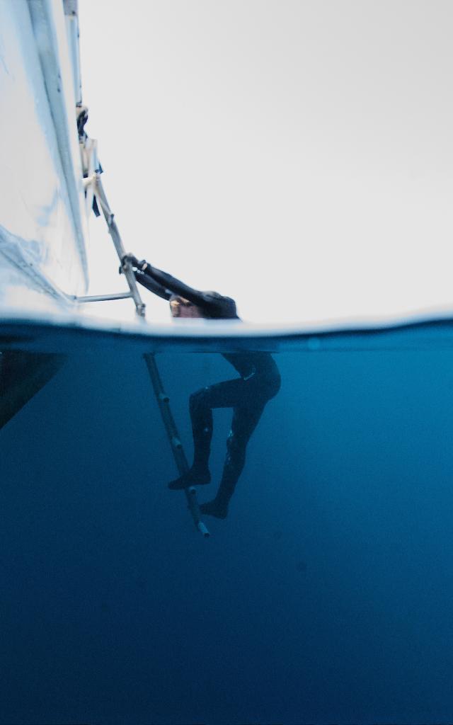 Plongeur qui remonte à bord d'un bateau