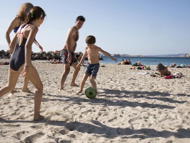 famille qui joue au ballon sur la plage à Marseille