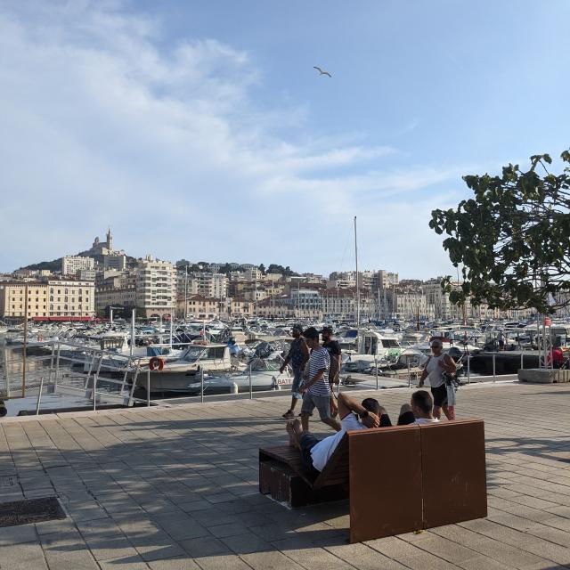 Personnes assises à l'ombre sur le Vieux-Port